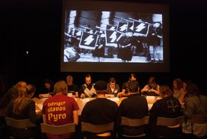 A group of people sitting around a table reading from papers. Bheind them a projection of a photograph of Hitler Jugend from Nazi Germany.