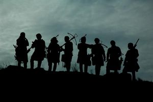 Silhouette of a group of eight medieval style soldiers with crossbows against a cloudy sky.