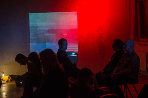Seven people sitting in chairs seen mostly in silhouette in a dark room with a red light and projection of a train on the wall.