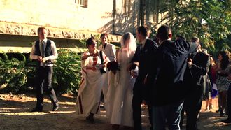 A group of people in festive clothing surrounding a couple on their wedding.