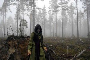 A green clad figure wearing a plague doctors mask standing in a foggy forest.