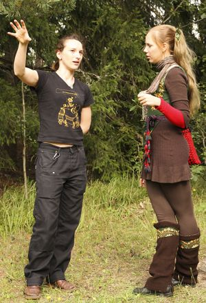 A photo of two people talking in front of a forest. The person on the left is wearing black and gesticulating. The person on the right is listening intently and wearing a medieval style fantasy outfit.